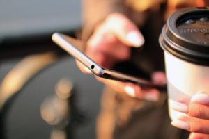 Bild på hand som håller mobil och latte