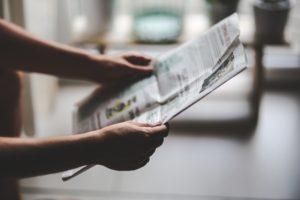Bild på händer som håller en tidning.
